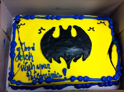 "A yellow and black Batman logo cake. Written on cake, ""Good luck with your poisonints."""