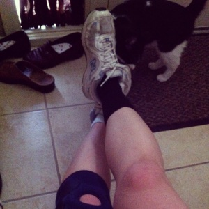 A woman's legs in ankle brace and knee brace and sneakers.