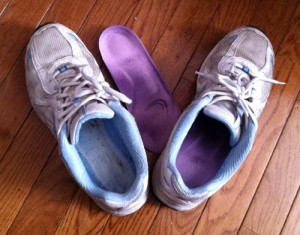 An aging pair of sneakers with one shoe insert on the floor next to them